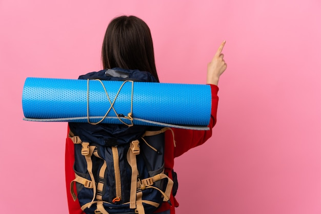 Bergbeklimmer meisje met een grote rugzak geïsoleerd op roze terug met de wijsvinger