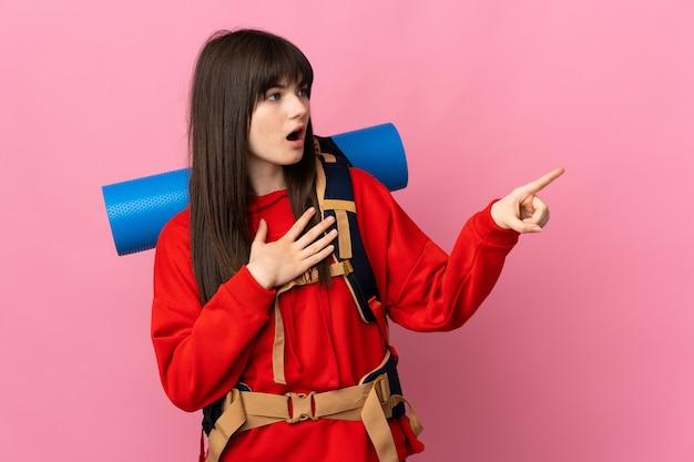 Bergbeklimmer meisje met een grote rugzak geïsoleerd op roze wijzende vinger naar de zijkant