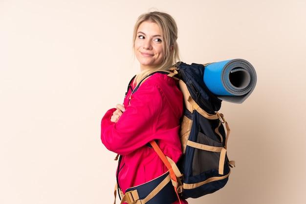 Bergbeklimmer vrouw met een grote rugzak over geïsoleerde muur lachen