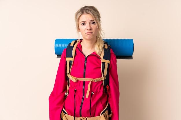 Bergbeklimmer vrouw met een grote rugzak over geïsoleerde muur triest