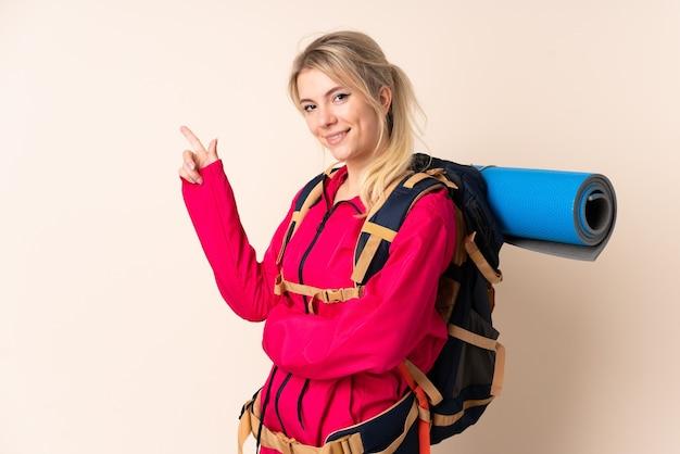 Bergbeklimmer vrouw met een grote rugzak over geïsoleerde muur wijzende vinger naar de zijkant