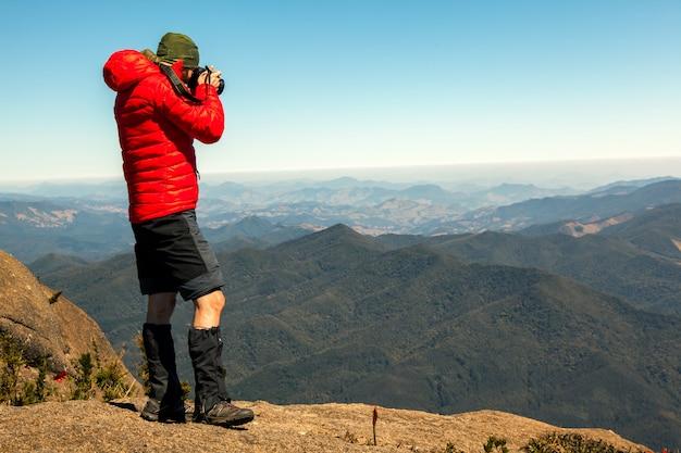 Bergbeklimmerfotograaf in de top van de rotsberg