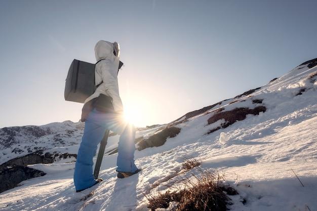 Bergbeklimmermens die aan de piekberg op de winter bij zonsondergang beklimmen