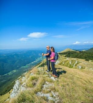 Bergbeklimmerpaar op het nanos-plateau in slovenië dat de mooie vipava-vallei bekijkt