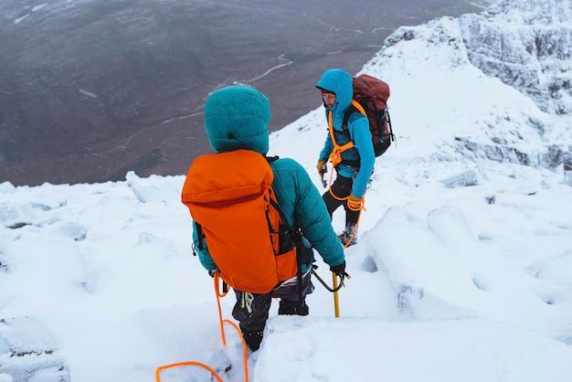 Bergbeklimmers die een besneeuwde liathach ridge in schotland beklimmen