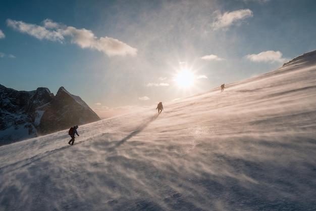 Bergbeklimmers die in blizzard sneeuwheuvel bij zonsondergang beklimmen