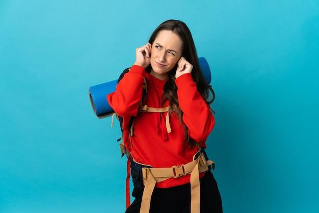 Bergbeklimmervrouw met een grote rugzak over geïsoleerde gefrustreerde achtergrond en die oren behandelt