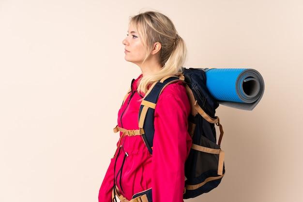Bergbeklimmervrouw met een grote rugzak over geïsoleerde muur die kant kijkt