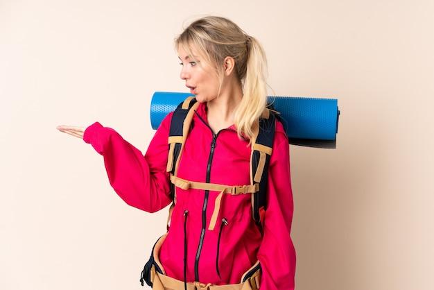 Bergbeklimmervrouw met een grote rugzak over geïsoleerde muur