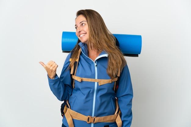 Bergbeklimmervrouw van middelbare leeftijd met een grote rugzak over geïsoleerde achtergrond die naar de zijkant wijst om een product te presenteren present