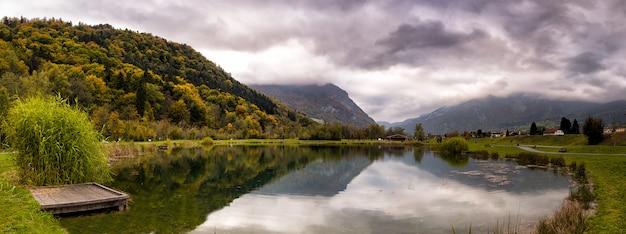 Bergbezinning op een meer met groene bomen in de alpen