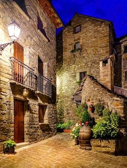 Bergdorp 's nachts. architectuur van stenen huizen, balkons met bloemen en verlichte steegjes. torla ordesa.