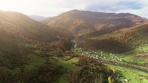 Bergdorpgebouwen bij rivier tegen bruine heuveltoppen
