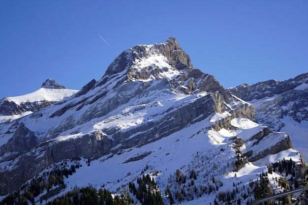 Bergen bedekt met sneeuw onder de zuivere blauwe lucht in de winter