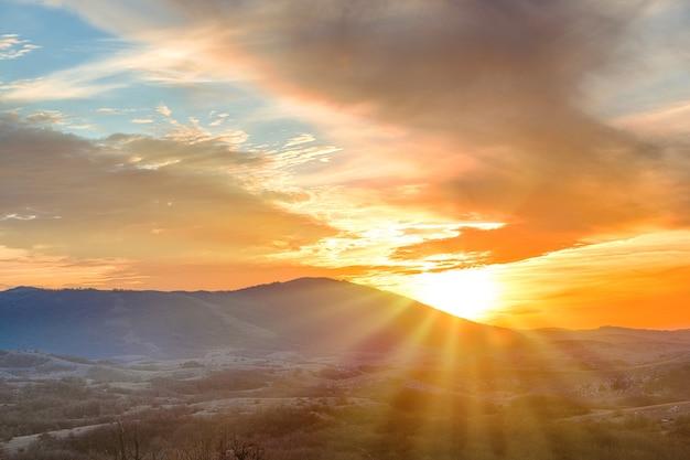 Bergen bij zonsondergang met dramatische kleurrijke wolken aan de hemel