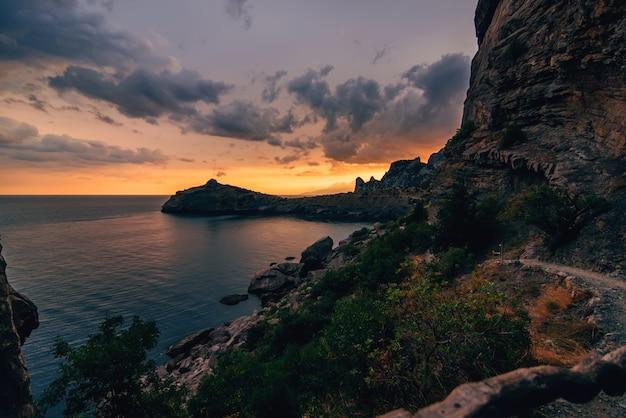 Bergen en de zee op oranjerode zonsondergang in de natuur