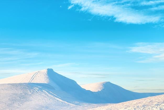 Bergen in sneeuw. landschap met zonsondergang over heuvels