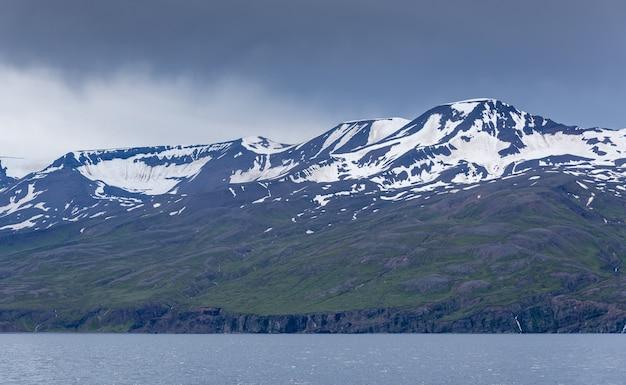Bergen met besneeuwde foto's bij de zee op een sombere dag in ijsland