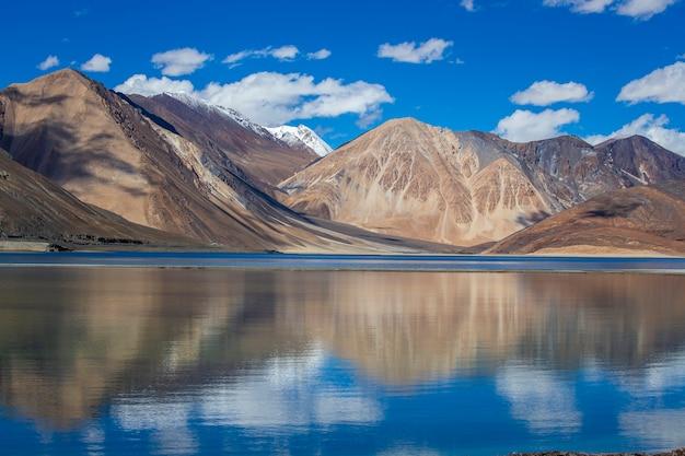 Bergen tegen de blauwe lucht en het meer pangong in de indiase himalaya