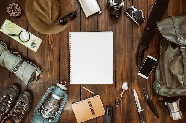 Bergen wandelen spullen gerangschikt op houten vloer. machete, laarzen, lantaarn, camera, hoed, kaart, kompas. kopieer ruimte. camping concept. safari briefkaart, poster, sjabloon voor spandoek.