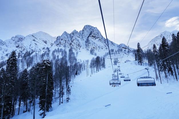 Berghelling in rosa khotor-skitoevlucht in rusland. vakantie en actieve rust in de bergen. winter koud seizoen en blauwe wolken aan de hemel.