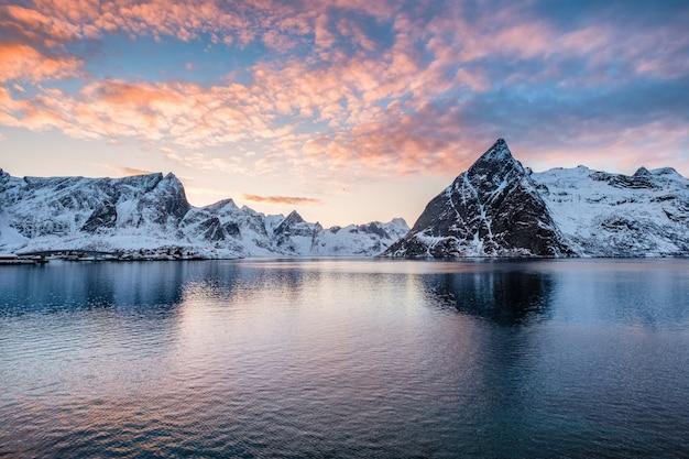 Bergketen met pluizige kleurrijke wolken in oceaan bij zonsondergang