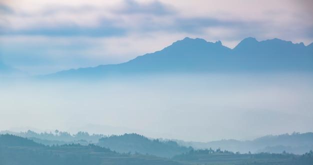 Bergketen met zichtbare silhouetten door de ochtend kleurrijke mist.