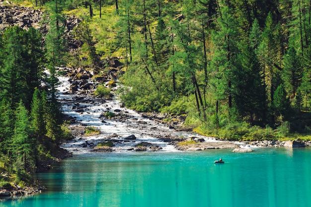 Bergkreek stroomt in meer. bekijk boven visser in boot op azuurblauwe water. prachtig bos in zonlicht. grote keien in beek. sfeervol mooi landschap van hooglandaard in zonnige dag.