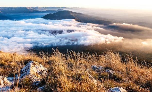 Berglandschap bij zonsondergang met lage wolken