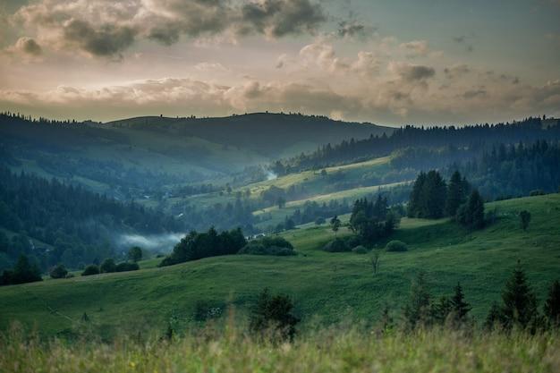 Berglandschap en weide verlicht door de zon bij zonsondergang