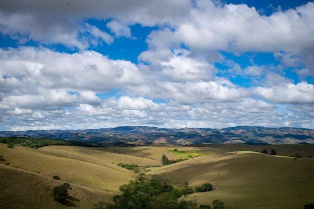 Berglandschap, heuvels en blauwe lucht met witte wolken