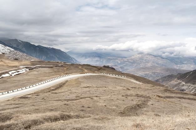 Berglandschap met alpine weg tegen de achtergrond van een sombere hemel