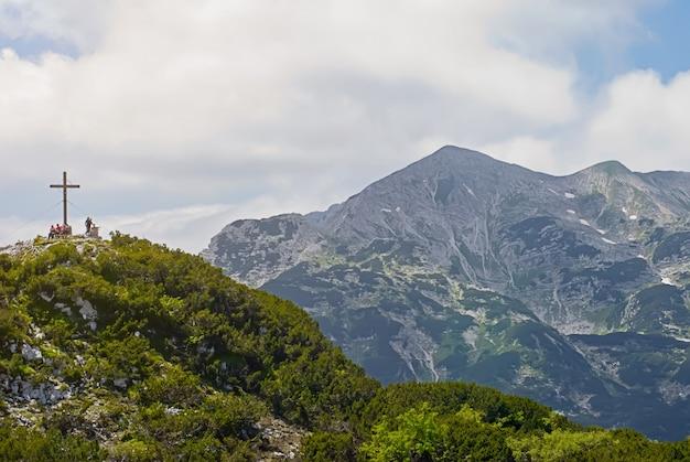 Berglandschap met kruis op piek in nationaal park, de bergen van alpen