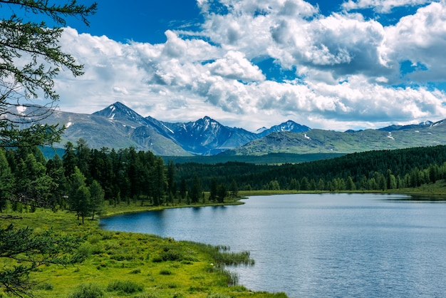 Berglandschap, witte wolken, meer en bergketen in de verte.