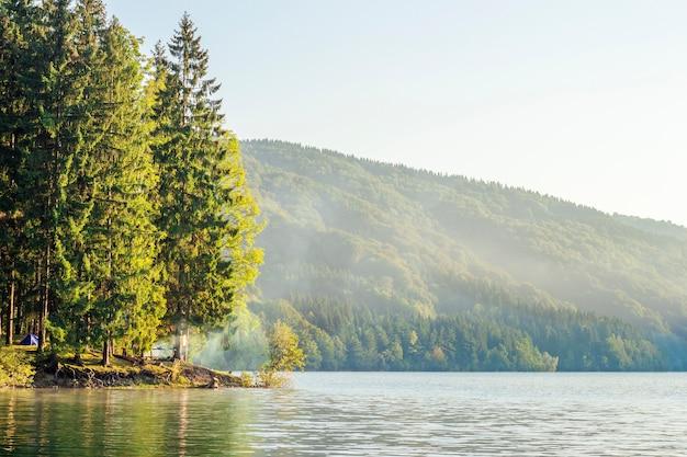 Bergmeer in de ochtend met bos en toeristische wandelkamp en vreugdevuur met rook