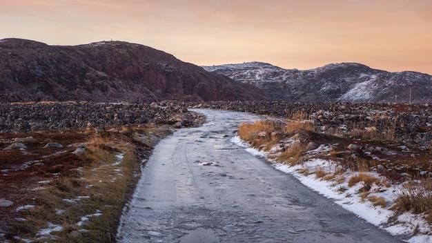 Bergpad. een kronkelend bergpad tussen de besneeuwde arctische heuvels. teriberka.