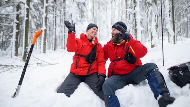 Bergreddingsdienst op operatie buiten in de winter in bos sneeuw graven met schoppen