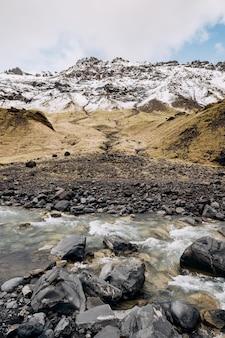 Bergrivier aan de voet van de berg met een besneeuwde top geel droog gras op de bergen