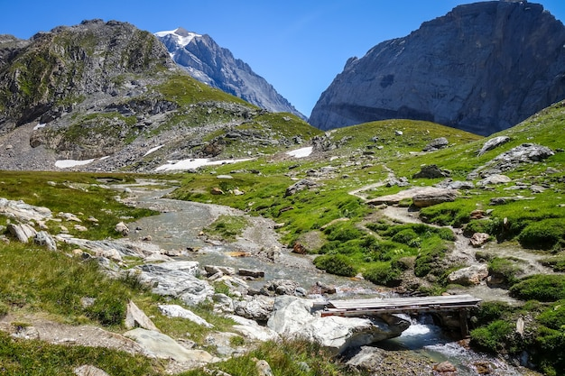 Bergrivier en houten brug in de alpiene vallei van het nationale park van vanoise, savoie, franse alpen