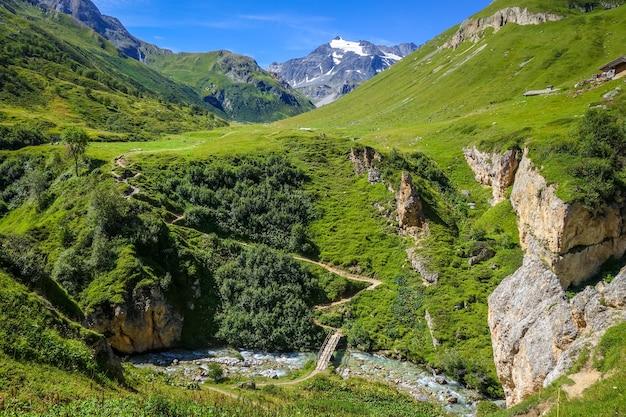 Bergrivier en houten brug in de alpiene vallei van het nationale park vanoise savoie franse alpen