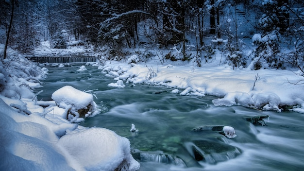 Bergrivier met stroomversnellingen, oevers bedekt met sneeuw. blauw helder water.