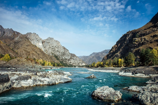 Bergrivier stroomt langs steenachtige oevers tussen rotsachtige bergen tegen een heldere blauwe hemel