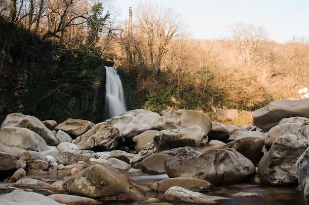 Bergrotsen op voorgrond en waterval die in rivier in martvili-canion stromen