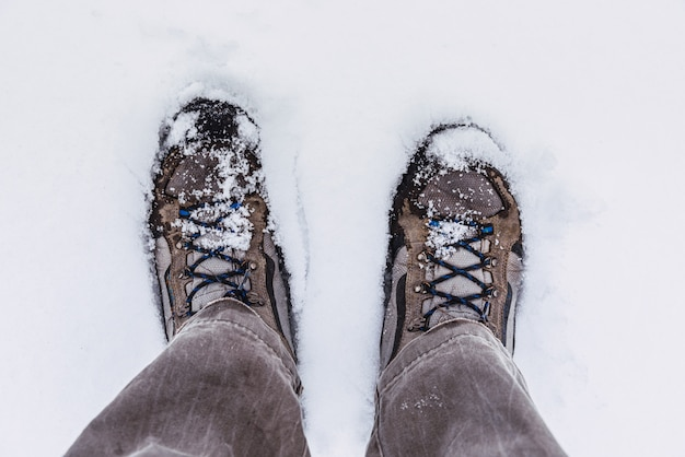 Bergschoenen in de sneeuw, gezien vanuit het zicht van de wandelaar.