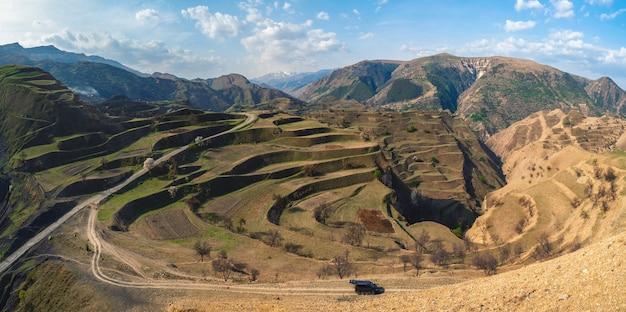 Bergterrein met een kleine minibus in de buurt van de berg. hoge bergen, complex berglandschap, groene terrassen bedekt met schaarse vegetatiehellingen. dagestan
