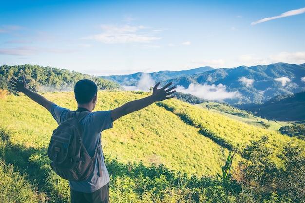 Bergtop. gelukkig man gebaar opgeheven armen. de grappige wandelaar met opgeheven dient de lucht op rotsrand in nationaal park in. levendig en sterk vignetteneffect.