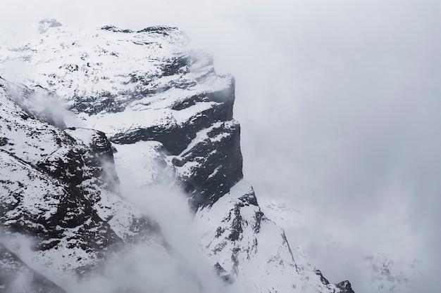 Bergtop in nepal. rotsberg met sneeuw in mist