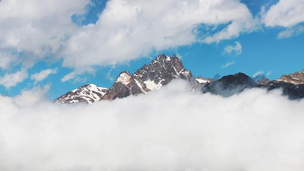 Bergtop panorama dat uit de wolken komt
