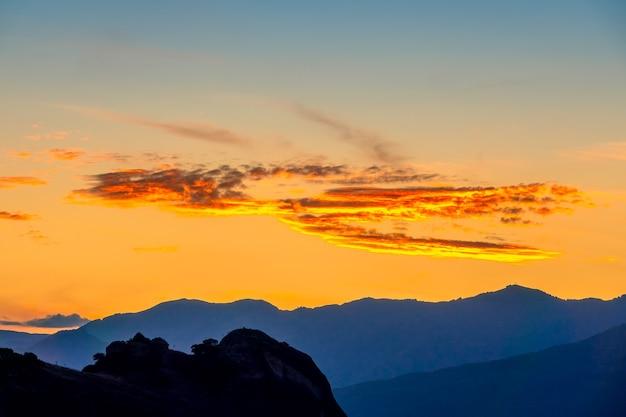 Bergtoppen en golden post-sunset sky