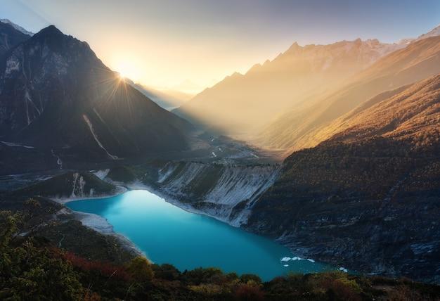 Bergvallei en meer met turkoois water bij zonsopgang in nepal